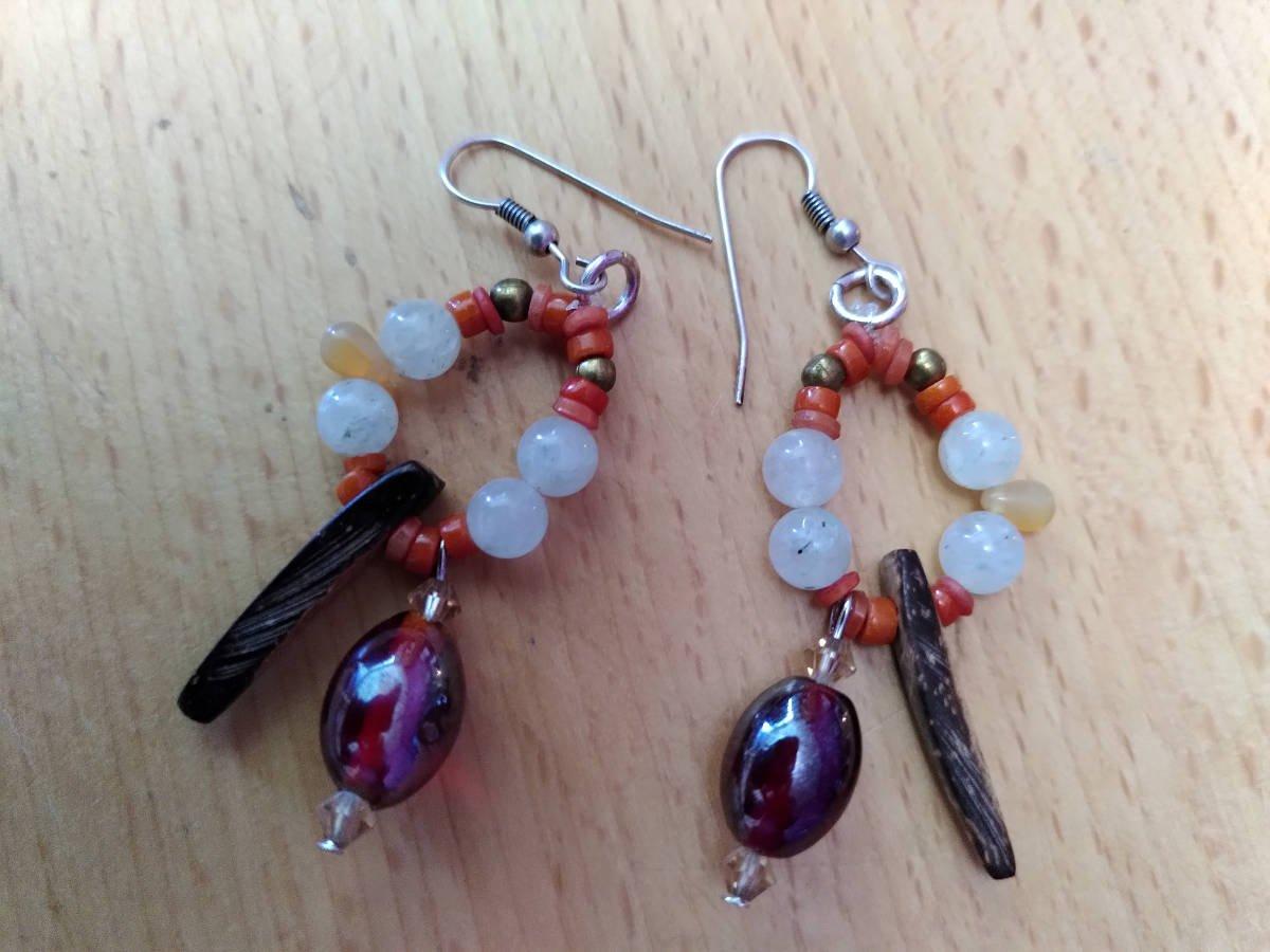 Paire de boucles d'oreille, en miroir ; dans chacune, il y un triangle de bois, une grosse perle pourpre entourée de cristaux saumon, de petites perles rondes blanches, une goutte orange, de toutes petites perles de corail et deux perles rondes dorées